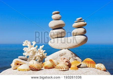 symbolic scales of white stones shells and coral on a background of the summer sea and blue sky. Concept of harmony and balance.