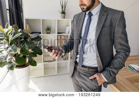 Partial View Of Businessman Holding Smartphone In Hand In Office