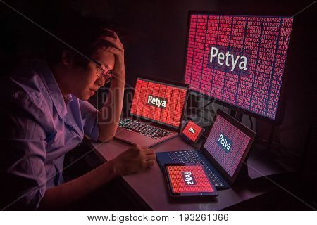 Young Asian male frustrated confused and headache by Petrwrap or Petya ransomware attack on desktop screen notebook and smartphone cyber attack and internet security concepts