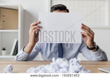 obscured view of businessman covering face with blank paper in hands