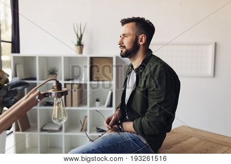 Pensive Bearded Man Holding Eyeglasses While Sitting At Table And Looking Away