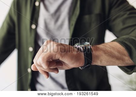 Cropped shot of man in shirt checking wristwatch indoors