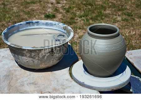 On the potter's wheel is a pot made of clay. On the table is a pelvis of water. In the water there are wooden template and a rubber scraper