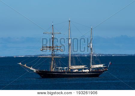 Large schooner sailing ship boat moored in ocean bay against blue sky