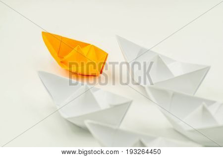 leader paper ship followed by other white ships
