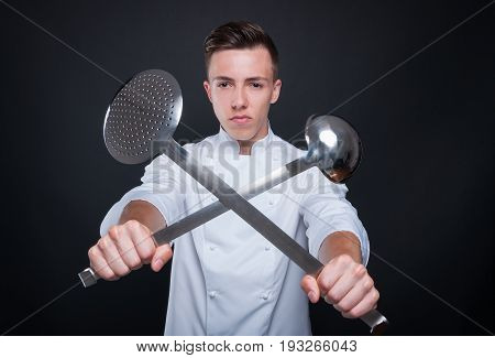 Portrait Of Chef Holding Crossed Ladle And Skimmer