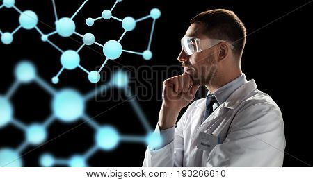 bio technology, science and people concept - male doctor or scientist in white coat and safety glasses looking at virtual projection of molecule over black background