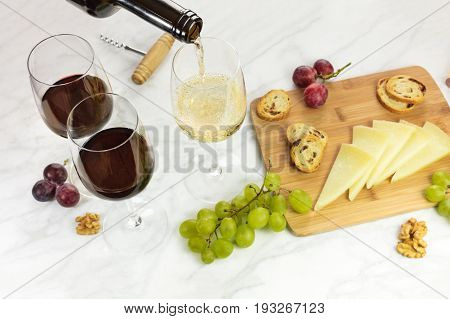 White wine poured into a glass at a tasting, with a cheese board with bread and grapes. Selective focus and a place for text