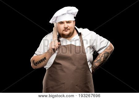 Confident Young Chef Holding Rolling Pin On Shoulder And Standing With Hand On Waist Isolated On Bla