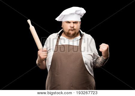 Angry Young Chef Holding Rolling Pin And Shaking Fist Isolated On Black