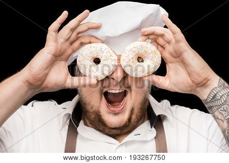 Excited Chef In Hat And Apron Looking Through Doughnuts Isolated On Black