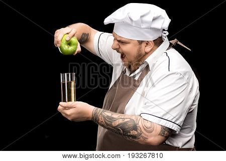 Side View Of Yelling Chef Holding Fresh Apple And Glass Of Juice Isolated On Black