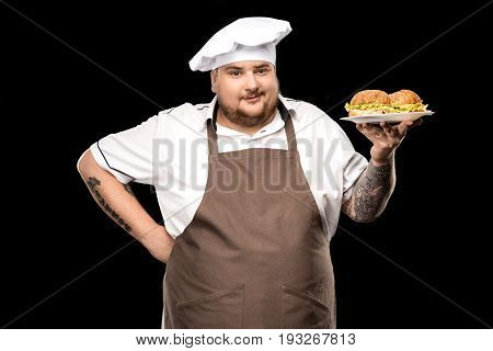 Cooker Holding Burgers On Plate And Looking At Camera Isolated On Black