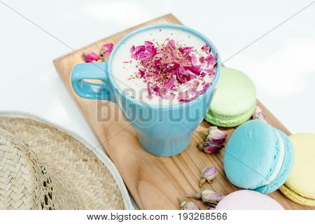 Closeup View On Straw Hat And Blue Cup Of Aroma Cappuccino With French Tasty Macarons