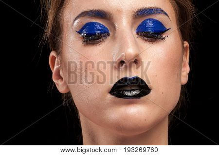 Beautiful woman wearing extravagant blue make up with black lips in studio photo. Beauty and fashion. Cosmetic and creative artistic make up
