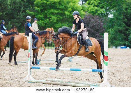 Horse rider is jumping over obstacles in the arena outdoors