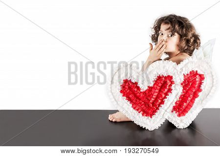Little Curly Angel Sitting On A Black Floor Half-turned And Sent A Kiss To The Camera. Close-up. Whi