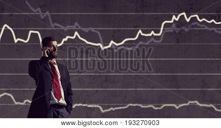 Businessman with smartphone standing over diagram background. Business, finance, investment concept.