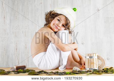 Cute Curly-haired Boy Shirtless In A Towel Sitting Hugging Legs Hands, Looking Into The Camera. Back