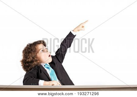 Little Curly Boy In A Business Suit Sitting At A Desk Holding Up A Hand And Points His Index Finger