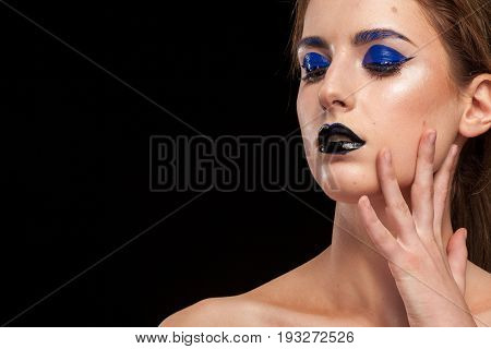 Model with extravagant fashion makeup posing in studio on black background. Beauty and fashion. Cosmetic and creative artistic make up