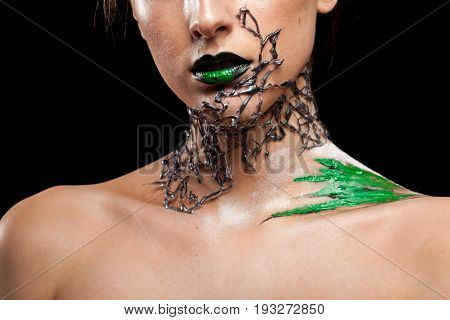 Woman with decorative creative fashion make up on black background in studio photo. Cosmetics and extravagant makeup