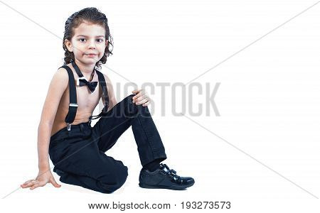 A Cute Boy In Suspenders Sits Bending His Leg And Looks Into The Camera. White Background.