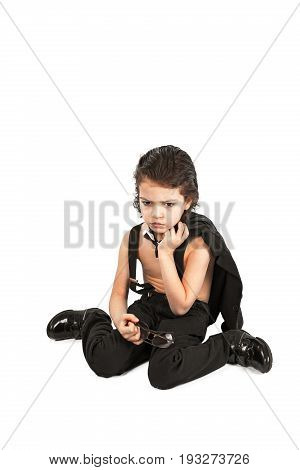 Offended brutal boy sits on the floor. White background.