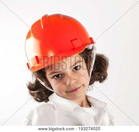 Young curly-haired boy in a helmet looks into the camera. Close-up. Gray background.