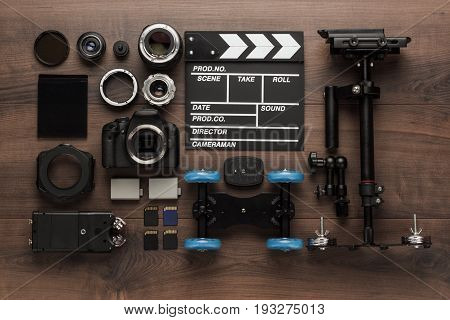 different film production equipment on the table. film production equipment for indie movie making. short movie creation tools. top view of film making tools for movie production. film making equipment on wooden background view from above. short movie pro
