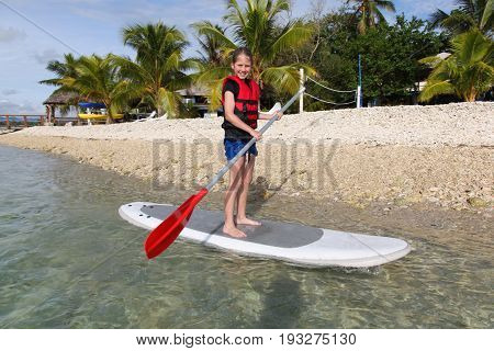 A young girl enjoying Stand Up Paddle Boarding in Vanuatu. Vanuatu is a popular tropical destination in the South Pacific