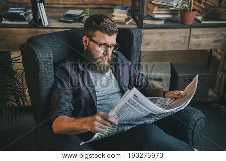 Serious Bearded Man In Eyeglasses Reading Newspaper While Sitting In Armchair At Home