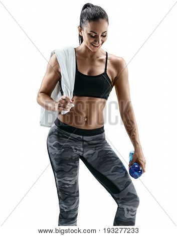 Resting time. Attractive smiling woman with towel on shoulders holding bottle of water. Health concept.