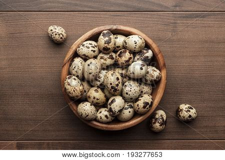 some quail eggs in wooden bowl. fresh quail eggs on the brown table. raw quail eggs on the wooden background. fresh quail eggs in wooden bowl top view