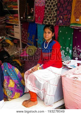 VARANASI VARANASI AREA STATE UTTAR-PRADESH INDIA - JANUARY 27 2014: A girl a teenager - a seller of fabrics in a street shop. Varanasi. The holy city for Buddhists the most holy place in Hinduism.