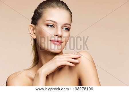 Beautiful blonde girl. Portrait of smiling girl on beige background. Youth and skin care concept