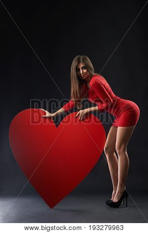 Vertical studio shot of a sexy seductive young woman in a red dress posing near a big red heart on black background love feelings emotions dating valentine concept.