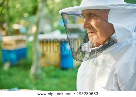 Close up portrait of a senior beekeeper wearing beekeeping suit looking away copyspace seniority pensioner elderly profession occupation hobby lifestyle farmer countryside retirement.