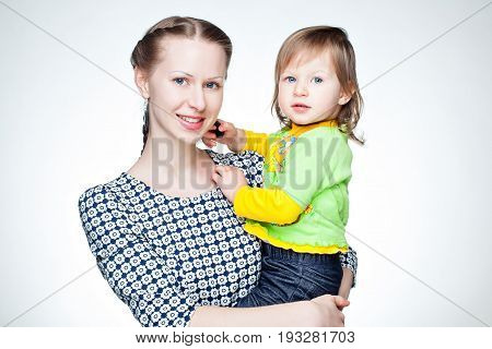 Mom holds daughter in her arms. And daughter is playing with mothers earrings.