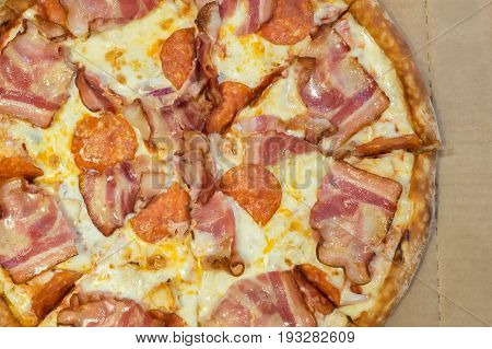 Serving Pizza with ham and cheese on cardboard. Delicious Italian fast food. Cakes for fun - no diet! Cakes for fun - no diet!