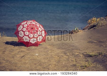 Lace fabric red umbrella on the beach on the background of the sea. Red umbrella on the sand