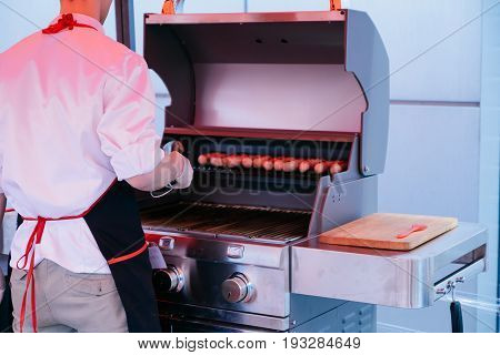 Grilling sausages on barbecue grill. BBQ in the garden. Bavarian sausages