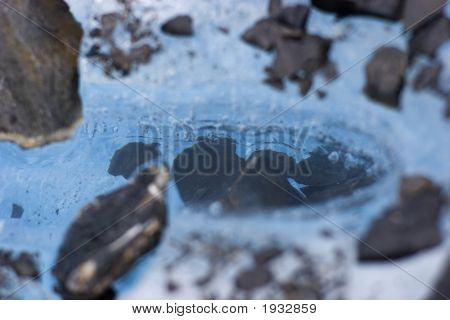 Cavity In Blue Glacial Ice Filled With Rocks