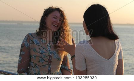 Beautiful young attractive women talking and smiling. Girls communicating with each other and standing near sea or ocean at summer.