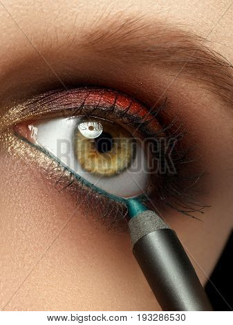 Make-up With Black Eyeliner Close-up. Make-up Artist Applying Eyeliner Pencil On A Model With Green