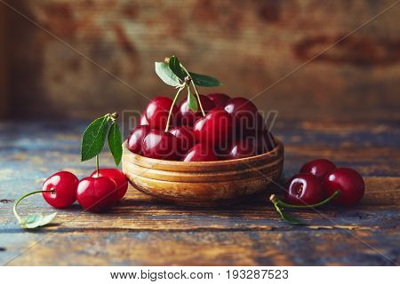 Cherries in a bowl on a wooden table. Freshly harvested cherries in a bowl on a wooden table.