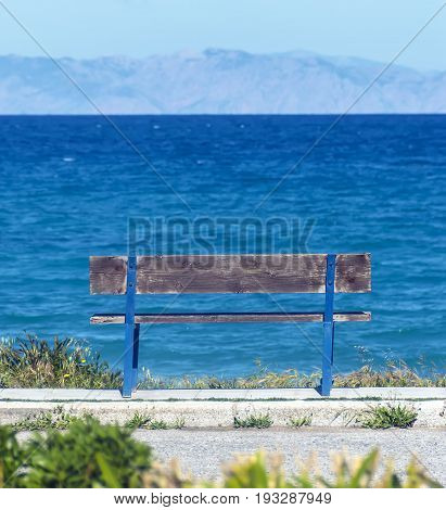 Old wooden bench overlooking the sea and mountains
