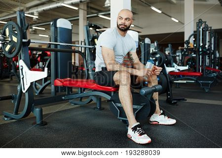 Portrait of handsome muscular sportsman sitting on weights bench in modern gym, looking away