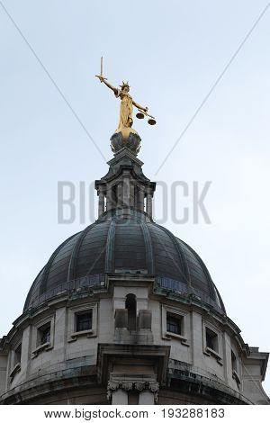 LONDON, GREAT BRITAIN - MAY 1, 2014: This is figure of Justice on the dome of the Old Bailey central criminal court.