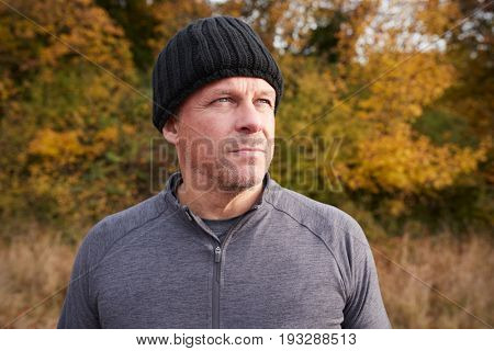 Mature Male Runner Pausing For Breath During Exercise In Woods